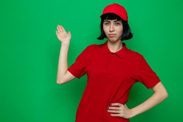 Confiante jeune livreuse caucasienne pointant vers l'arrière avec la main