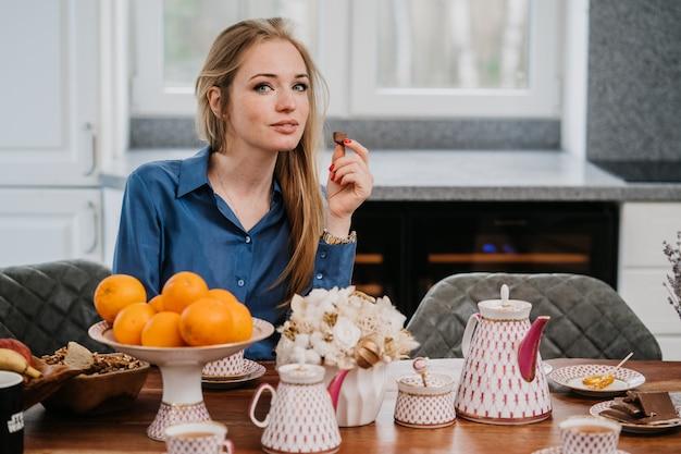 Confiante jolie femme blonde caucasienne portant une chemise bleue détient un morceau de chockolate, buvant du thé tout en prenant son petit déjeuner dans une chambre confortable. concept de personnes à la maison.