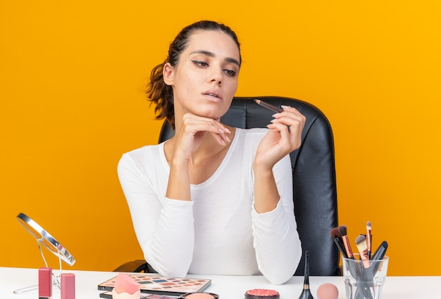 Confiante jolie femme caucasienne assise à table avec des outils de maquillage tenant et regardant l'eye-liner