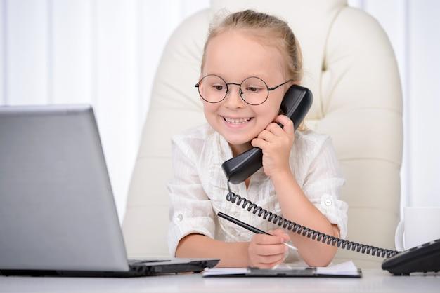 Confiante petite fille à lunettes parlant au téléphone.