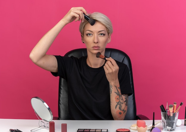 Confiante à la recherche d'une belle jeune fille assise à table avec des outils de maquillage appliquant un fard à joues en poudre avec un pinceau à poudre isolé sur un mur rose
