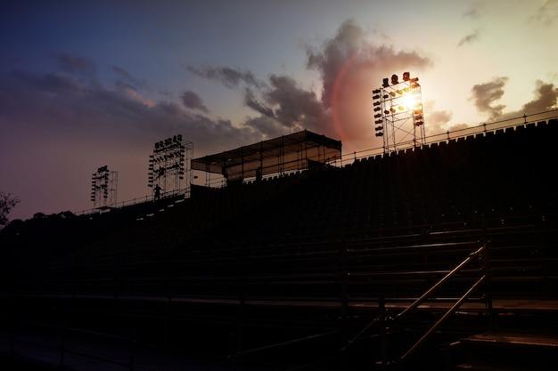 Une configuration d'échafaudage complexe pour une scène pour un concert en plein air vu au coucher du soleil