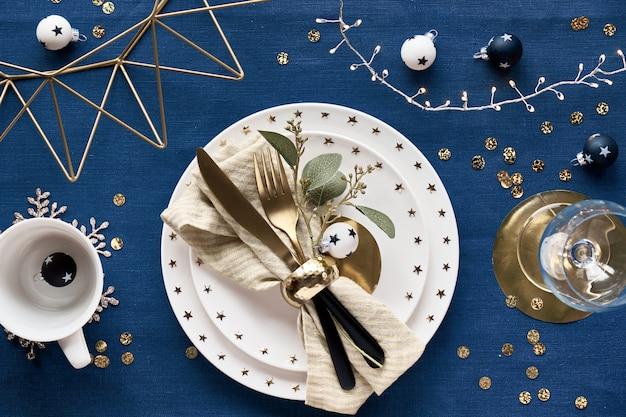 Configuration de table de noël avec assiette blanche, ustensiles dorés et décor de fil métallique géométrique doré. mise à plat sur textile en lin de couleur bleu foncé classique.