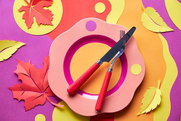 Configuration de la table pour la célébration de l'automne. assiette en plastique brillant sur papier coloré avec du papier feuilles d'automne