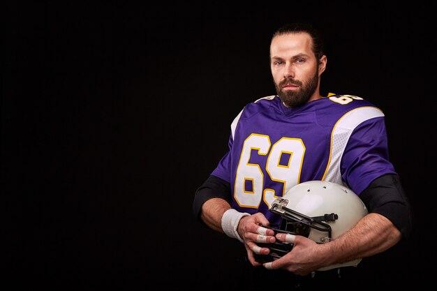 Configuré pour le jeu. joueur de football américain et tenant un casque dans sa main tout en se tenant contre le mur noir, copiez l'espace.