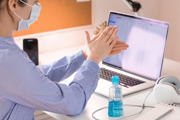 Confinement lié au coronavirus. femme d'affaires travaillant à domicile avec masque en quarantaine. gros plan sur les mains avec du gel désinfectant.