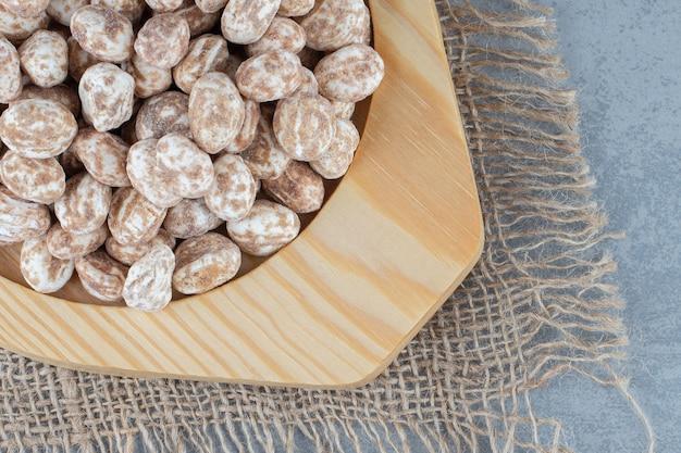 Confiserie dans l'assiette en bois, sur le dessous de plat, sur la table en marbre.
