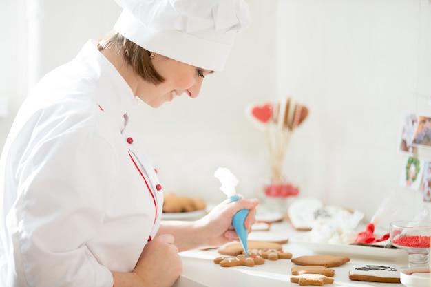 Confiserie souriante professionnelle décorant un gingerman