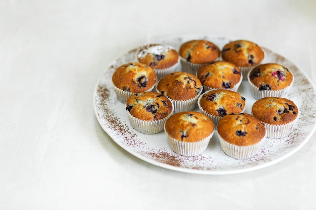 Confiseur arrose des muffins fraîchement cuits avec du sucre glace. pâtisseries sucrées, recettes, cuisine