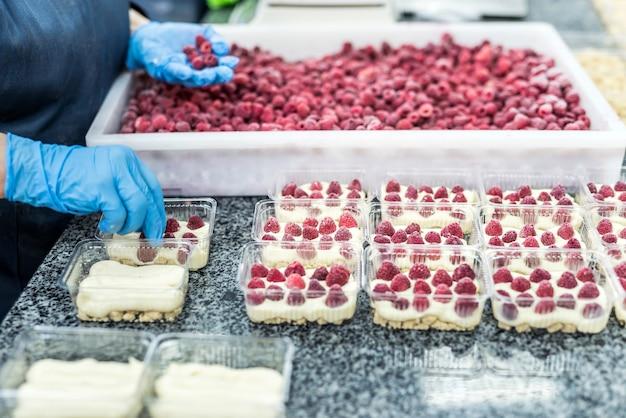 Confiseur décorant de délicieux desserts à la framboise en usine. nourriture délicieuse incroyable