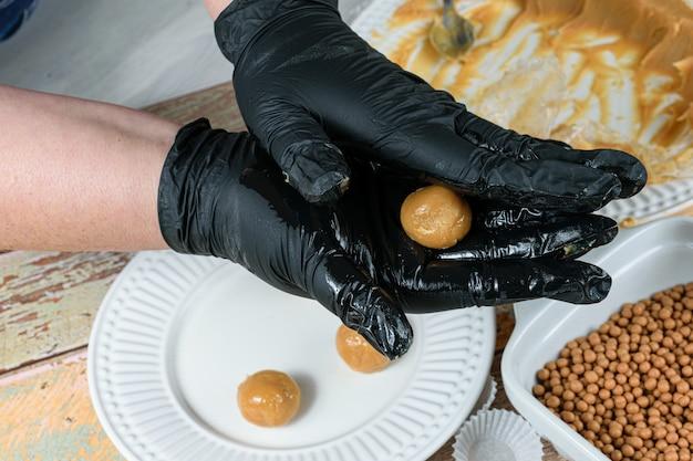 Confiseur avec des gants noirs faisant brigadeiro (brigadier) de dulce de leche.