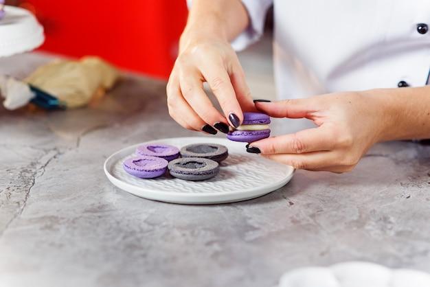 Le confiseur joint les parties des macarons entre eux à l'aide d'une crème. bouchent les mains du boulanger faisant des macarons.