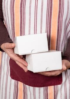 Confiseur ou livrer tenant deux boîtes de papier blanc sur fond blanc.
