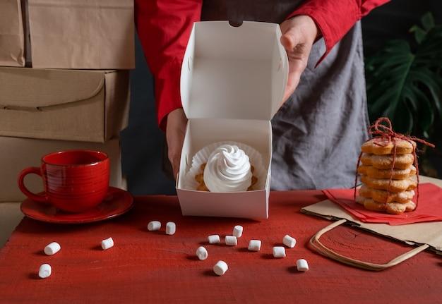 Confiseur tenant une boîte de papier blanc avec un gâteau blanc près de la table rouge.