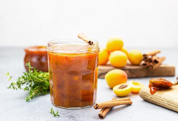 Confiture d'abricots dans un bocal en verre, abricots frais, thym et cannelle sur surface grise