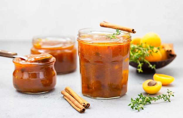 Confiture bio maison dans des bocaux en verre, abricots mûrs, cannelle et thym sur surface grise