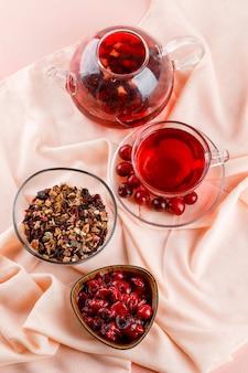 Confiture de cerises aux cerises, thé, herbes séchées dans un bol sur textile et rose