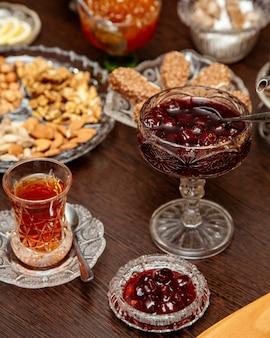 Confiture de cerises cornéliennes servie dans un plat en cristal avec du thé