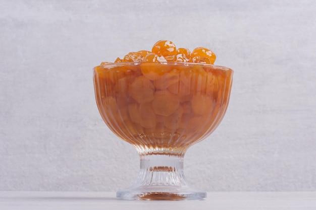 Confiture de cerises en verre sur tableau blanc.