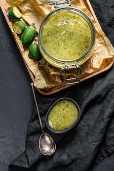 Confiture de feijoa verte sur une planche à découper en bois dans un bocal en verre. dessert maison naturel. fond noir. vue de dessus