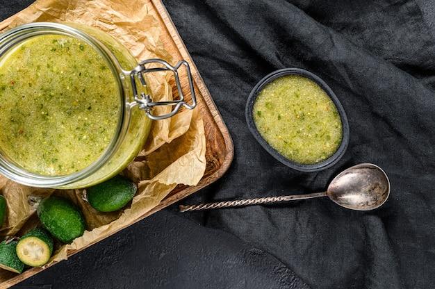 Confiture de feijoa verte sur une planche à découper en bois dans un bocal en verre. dessert maison naturel