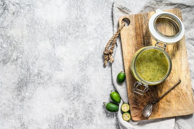 Confiture de feijoa verte sur une planche à découper en bois dans un bocal en verre.