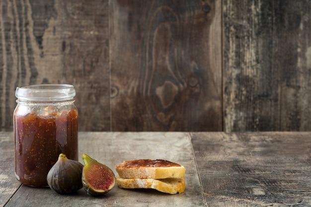 Confiture de figue sucrée dans un bocal sur l'espace de copie de la table en bois