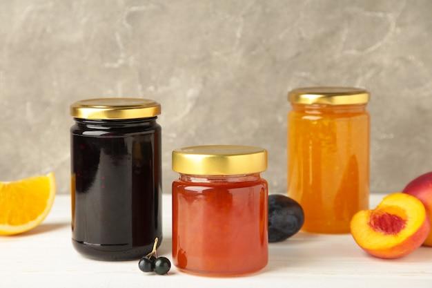 Confiture de fruits maison dans le pot avec des fruits frais et des baies sur fond gris.