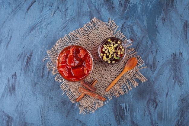 Confiture de fruits sucrée avec une tasse en verre de tisane et des bâtons de cannelle.