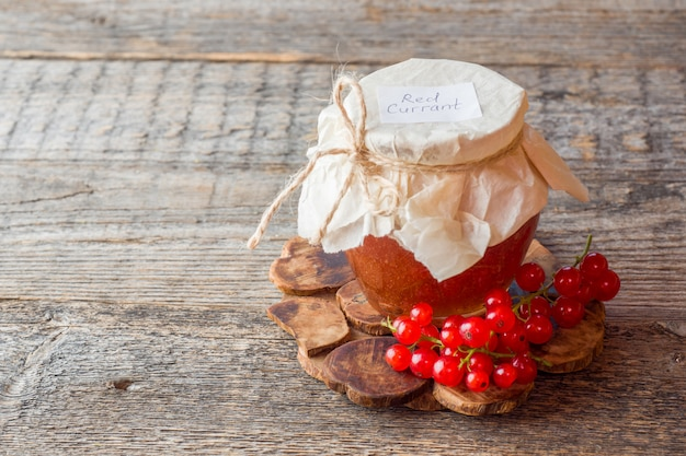 Confiture de groseilles utile dans un bocal en verre. groseilles fraîches