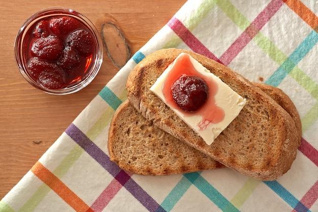 Confiture maison dans un bocal en verre avec une cuillère rouge et du pain à moitié mangé