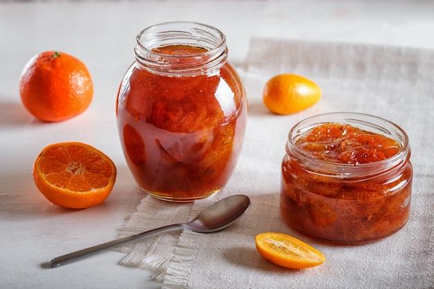 Confiture de mandarine et de kumquat dans un bocal en verre sur une table blanche.