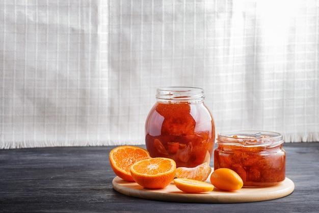 Confiture de mandarine et kumquat dans un bocal en verre sur une table en bois noire et lin blanc