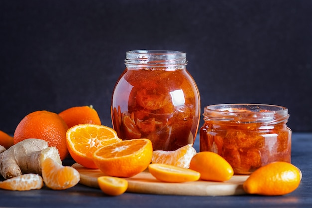Confiture de mandarine et de kumquat dans un bocal en verre sur une table en bois noire.