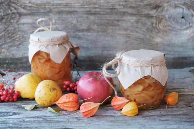 Confiture de poire dans des bocaux en verre, poires, groseilles du cap et frêne rouge sur une planche de bois