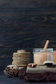 Confiture de poire épicée dans un bocal en verre, des craquelins, des épices et du thym. pierre brune.