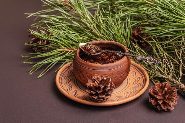 Confiture de pomme de pin sucrée. dessert traditionnel sibérien, branches fraîches à feuilles persistantes. fond de béton de pierre noire, espace de copie
