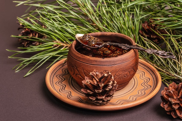 Confiture de pomme de pin sucrée. dessert traditionnel sibérien, branches fraîches à feuilles persistantes. fond de béton de pierre noire, gros plan