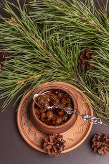 Confiture de pomme de pin sucrée. dessert traditionnel sibérien, branches fraîches à feuilles persistantes. fond de béton de pierre noire, vue de dessus