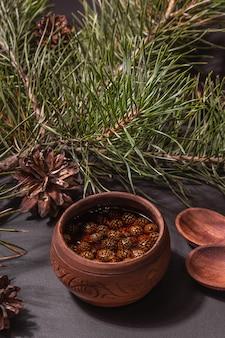Confiture de pomme de pin sucrée. dessert traditionnel sibérien, branches fraîches à feuilles persistantes. lumière dure à la mode, ombre sombre. fond de béton de pierre noire, mise à plat