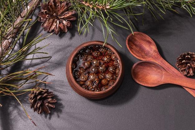 Confiture de pomme de pin sucrée. dessert traditionnel sibérien, branches fraîches à feuilles persistantes. lumière dure à la mode, ombre sombre. fond de béton de pierre noire, vue de dessus