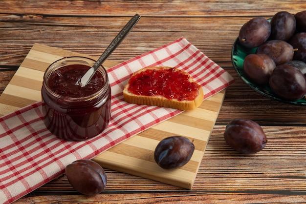 Confiture de prune dans le bocal en verre et sur le pain grillé sur le torchon à carreaux.