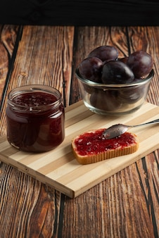 Confiture de prunes dans le bocal en verre et sur les toasts.