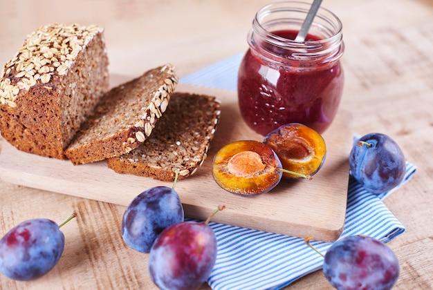 Confiture de prunes maison avec du pain frais sur une planche à découper