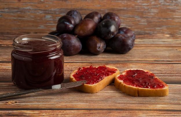 Confiture de prunes avec pain grillé et fruits sur une table en bois.