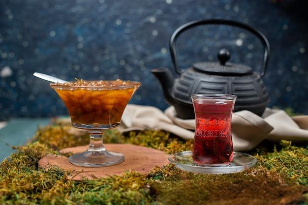 Confiture, verre à thé et bouilloire sur le plateau d'herbe