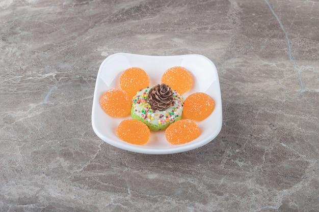 Des confitures et un beignet orné d'une pomme de pin sur un plateau sur une surface en marbre