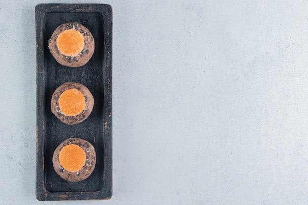 Des confitures et un biscuits aux pépites de chocolat empilés sur un plateau sur fond de marbre.