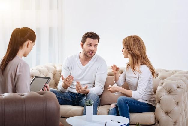Conflit familial. jeune couple émotionnel en colère se regardant et gesticulant tout en ayant une querelle