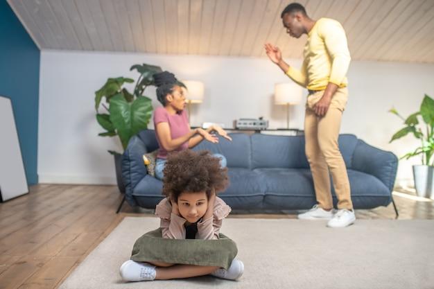 Conflit. de jeunes parents à la peau foncée jurant nerveusement à l'arrière de la pièce sur un canapé et leur petite fille malheureuse aux oreilles fermées assise sur le sol